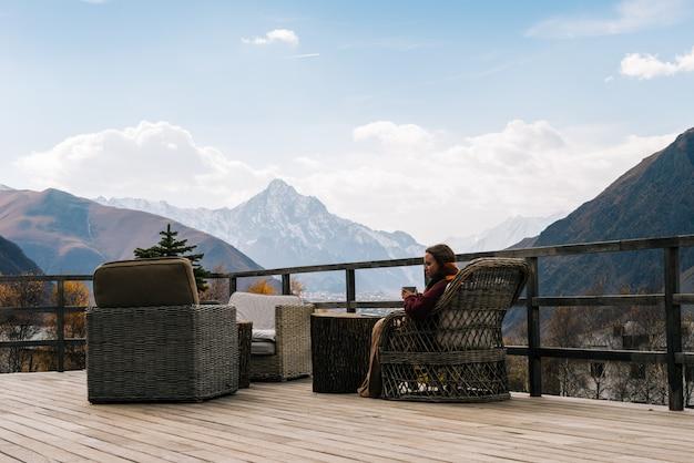 Une jeune fille voyage, s'assoit sur une véranda et profite d'une vue sur les montagnes