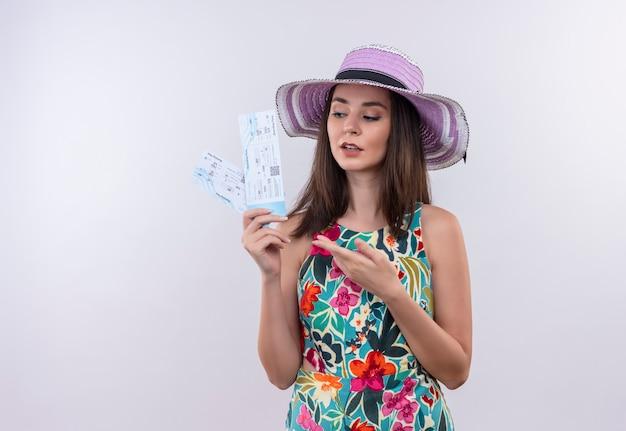 Jeune fille de voyageur caucasien tenant des billets montrant avec la main à des billets sur fond blanc isolé
