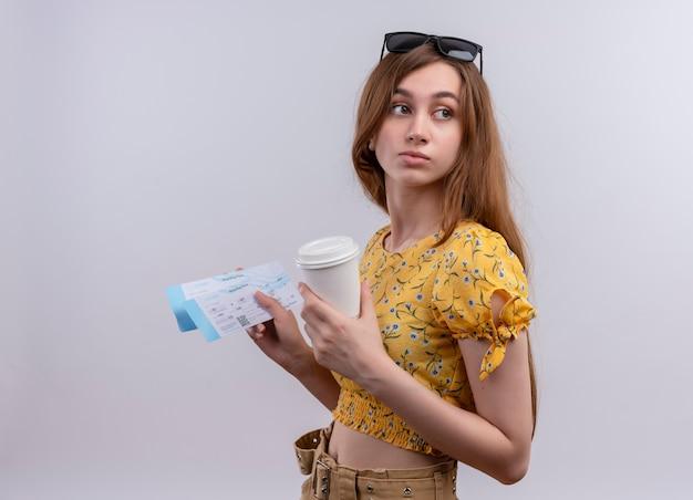 Jeune fille de voyageur portant des lunettes de soleil sur la tête tenant des billets d'avion et une tasse de café en plastique et regardant des billets debout en vue de profil sur un mur blanc isolé