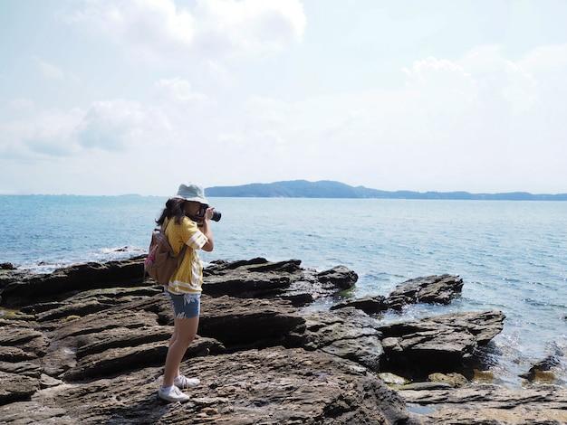 Jeune fille voyageur prenant des photos de la plage de l'été.