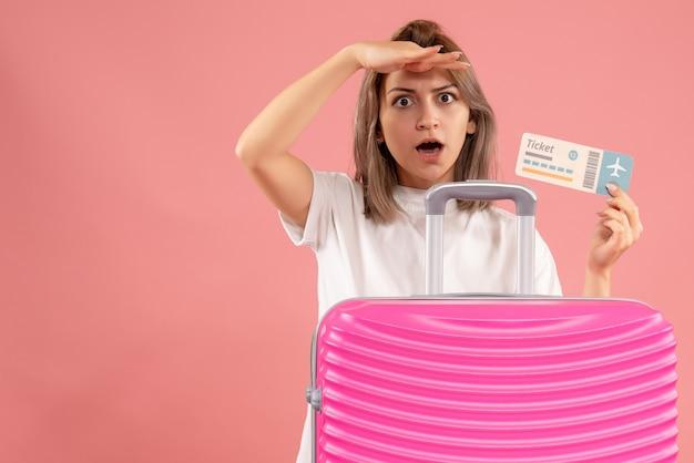 Jeune fille vue de face avec une valise rose tenant un billet observant