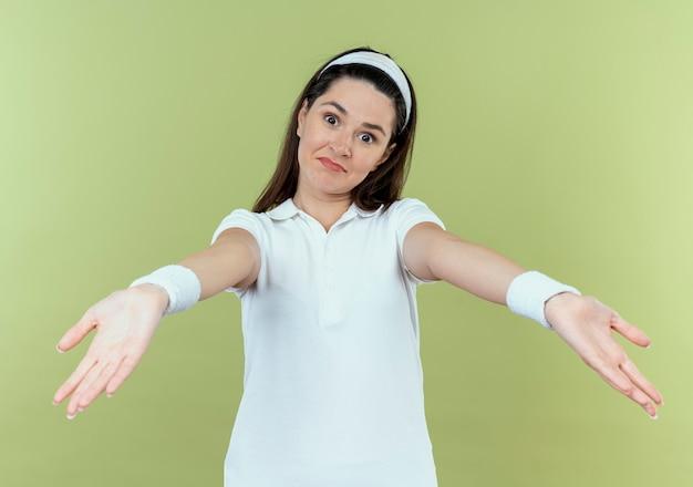 Jeune, fitness, femme, dans, bandeau, heureux, et, positif, faire, accueil, geste, à, mains, debout, sur, mur clair