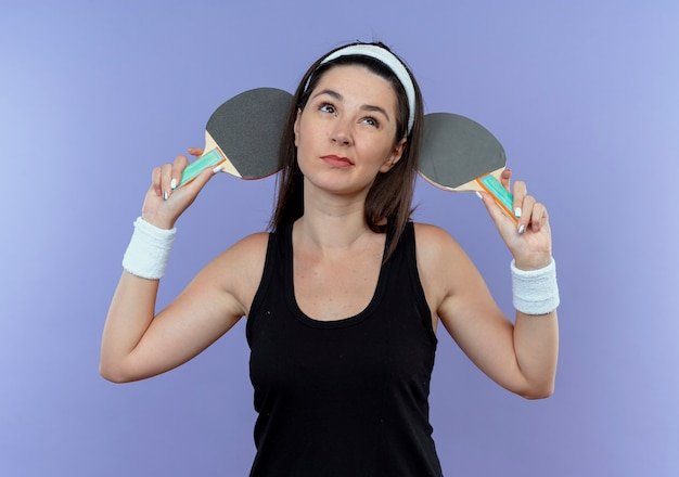 Jeune, fitness, femme, dans, bandeau, tenue, raquettes, pour, tennis, table, regarder, perplexe, debout, sur, mur bleu
