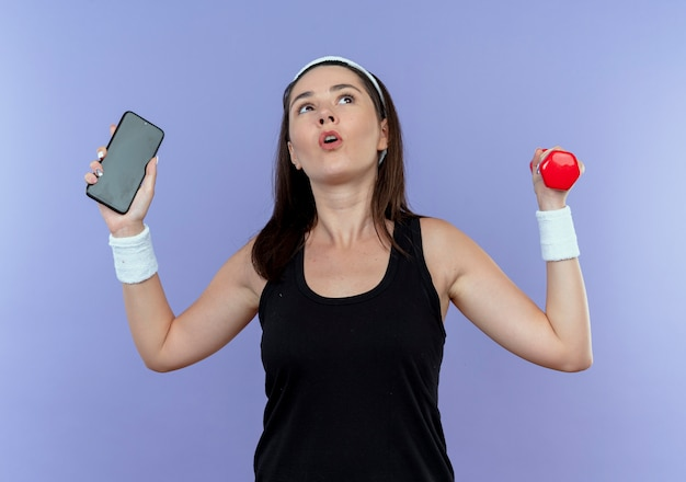 Jeune, fitness, femme, dans, bandeau, tenue, smartphone, et, haltère, à, confus, debout, sur, mur bleu