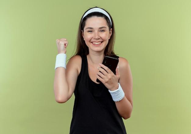 Jeune, fitness, femme, dans, bandeau, tenue, smartphone, serrer, poing, heureux, et, excité, debout, sur, mur clair