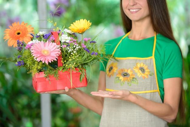 Jeune fleuriste femme souriante travaillant dans la serre.