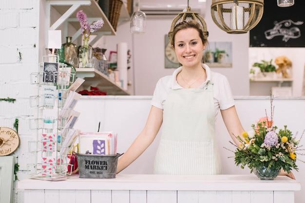 Jeune fleuriste posant près du comptoir