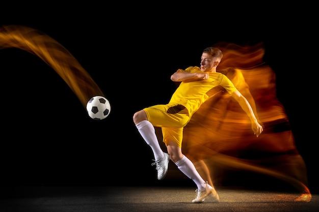 Jeune footballeur ou footballeur masculin de race blanche donnant un coup de pied au ballon pour le but en lumière mixte sur un mur sombre concept de passe-temps sportif professionnel de mode de vie sain