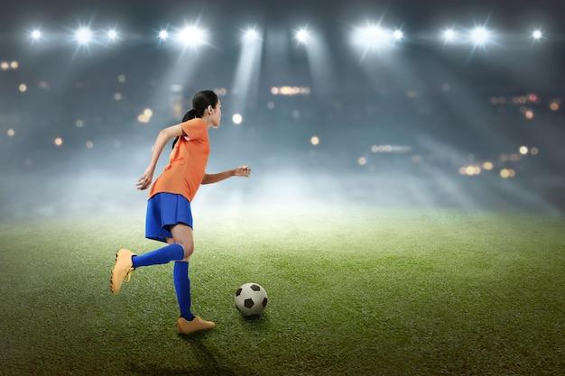 Jeune footballeuse asiatique femme botter le ballon