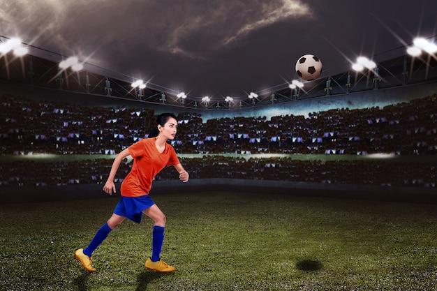 Jeune footballeuse asiatique qui veut donner un coup de pied au ballon