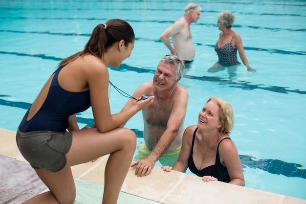Jeune formatrice discutant du timing avec les nageurs seniors au bord de la piscine