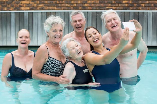 Jeune formatrice prenant selfie avec des nageurs seniors dans la piscine