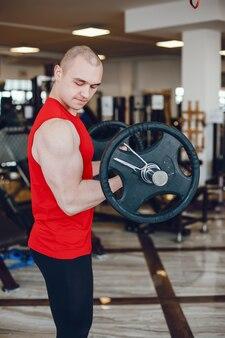 Jeune et fort gars s'entraîne dans la salle de gym