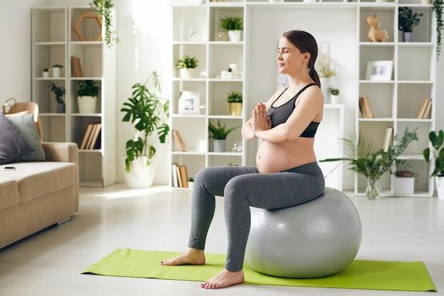 Jeune future mère sereine en vêtements de sport assis sur le fitball avec ses mains par la poitrine pendant la formation de yoga dans l'environnement familial