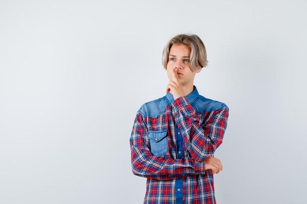Jeune garçon de l'adolescence avec des doigts dans un geste d'arme à feu sur la bouche