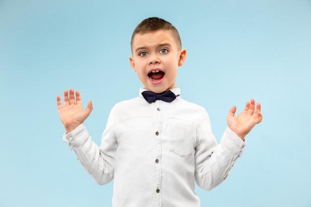 Le jeune garçon adolescent attrayant à la surprise isolé sur bleu