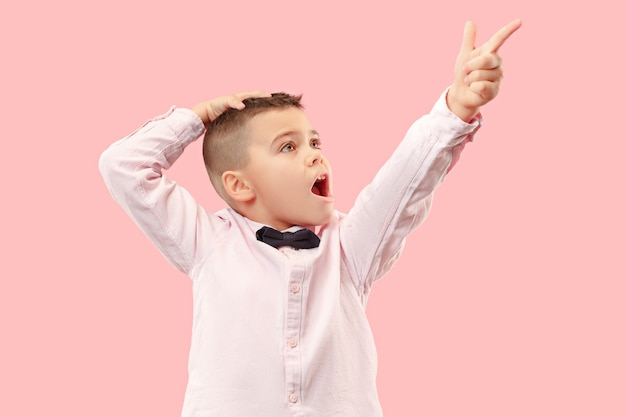 Le jeune garçon adolescent attrayant à la surprise isolé sur rose