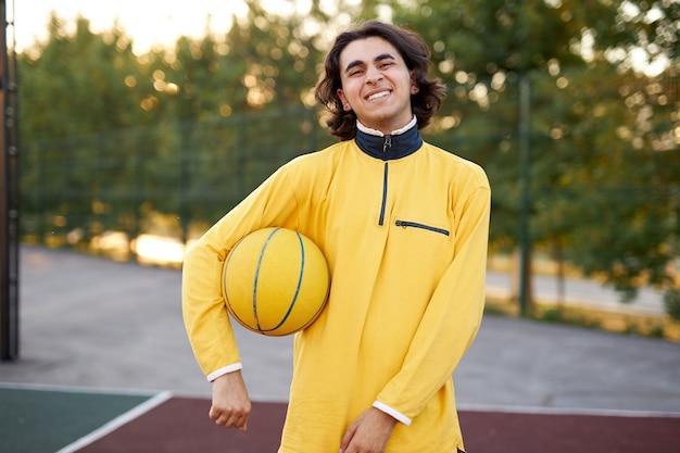 Jeune garçon adolescent caucasien jouant au basket