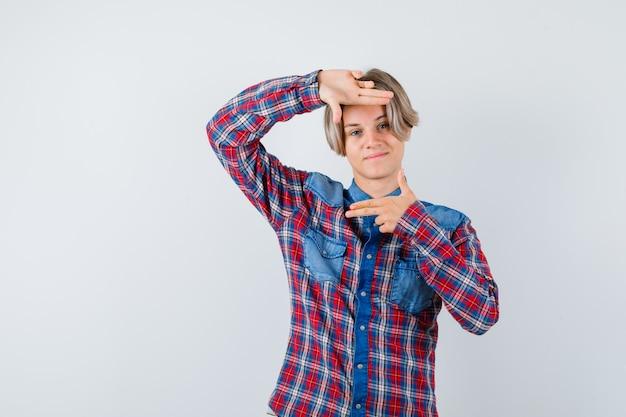Jeune garçon adolescent faisant un geste de cadre en chemise à carreaux et à la gaieté