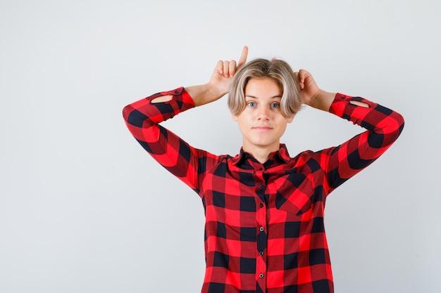 Jeune garçon adolescent gardant les doigts derrière la tête comme des cornes en chemise à carreaux et à la vue ludique, de face.