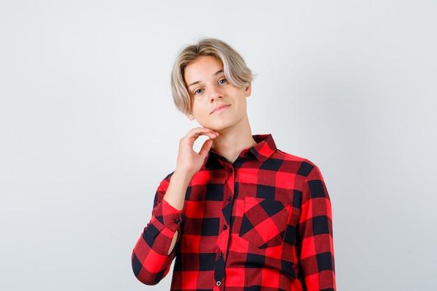 Jeune garçon adolescent gardant la main sous le menton en chemise à carreaux et l'air fier, vue de face.