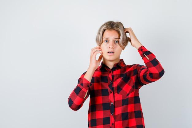 Jeune garçon adolescent gardant les mains sur la tête en chemise à carreaux et ayant l'air effrayé, vue de face.