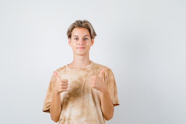 Jeune garçon adolescent en t-shirt montrant le double pouce vers le haut et regardant jolly , vue de face.