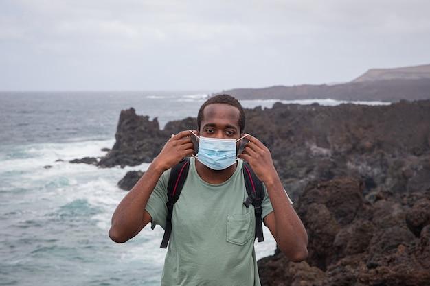 Un jeune garçon africain met un masque chirurgical avec ses mains à l'extérieur près de l'océan à lanzarote