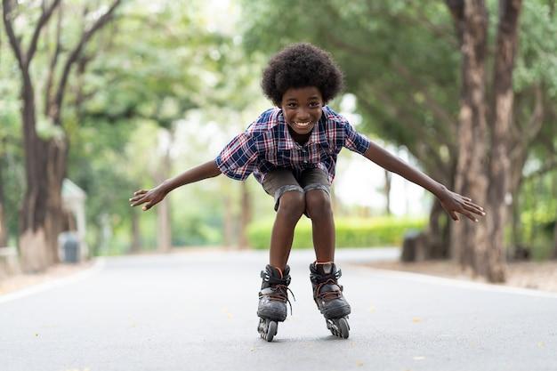 Jeune garçon afro-américain à cheval sur des patins à roulettes ou des patins à roulettes à l'extérieur.