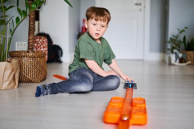 Jeune garçon d'âge préscolaire joue avec un jouet et s'amuse à la maison