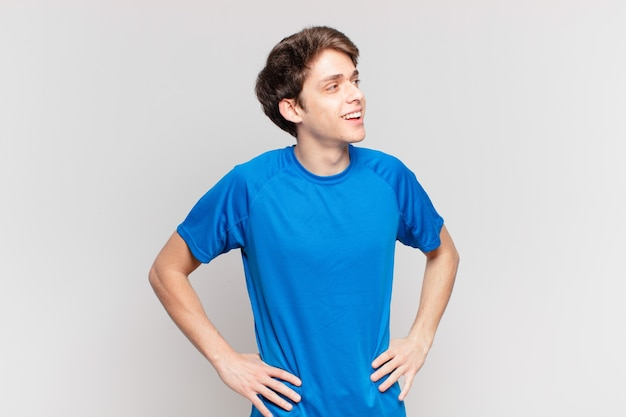 Jeune garçon à l'air heureux, joyeux et confiant, souriant fièrement et regardant de côté avec les deux mains sur les hanches
