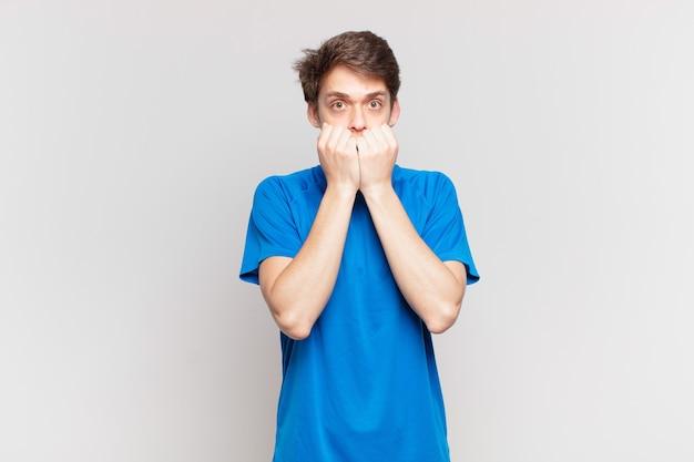 Jeune garçon à l'air inquiet, anxieux, stressé et effrayé, se rongeant les ongles et regardant vers l'espace de copie latéral