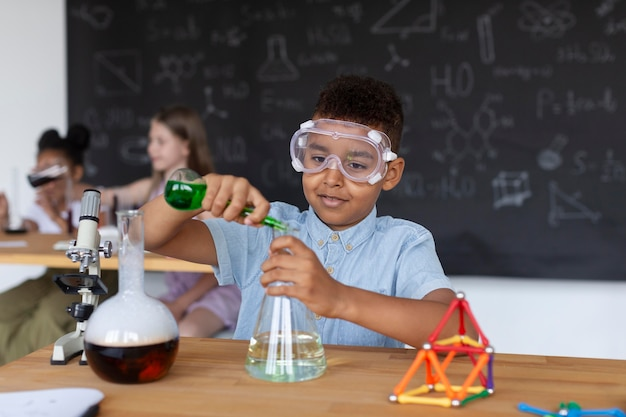 Jeune garçon apprenant plus sur la chimie en classe