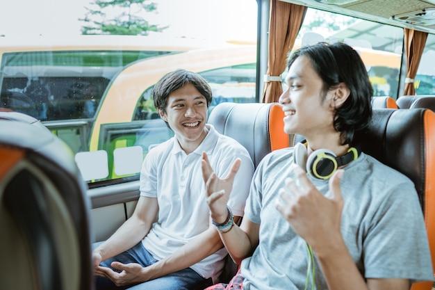 Un jeune garçon asiatique discutant avec un homme avec des écouteurs assis près de la fenêtre du bus