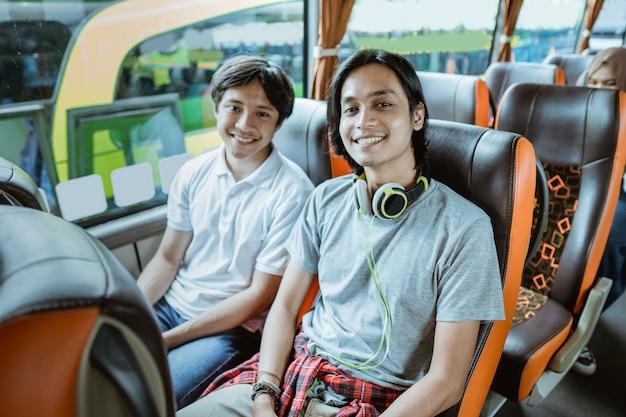 Un jeune garçon asiatique et un homme avec un casque souriant dans la caméra alors qu'il était assis près de la fenêtre du bus