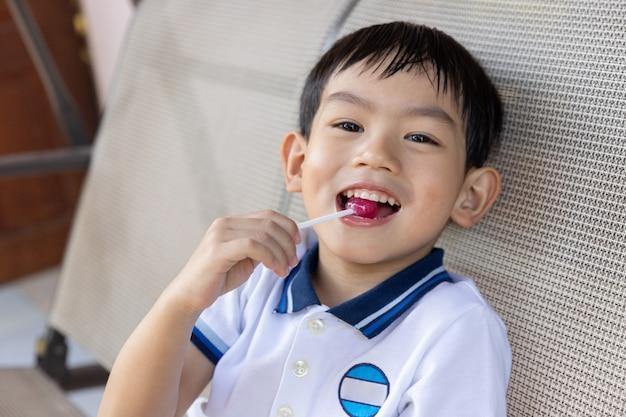 Jeune garçon asiatique mangeant une sucette