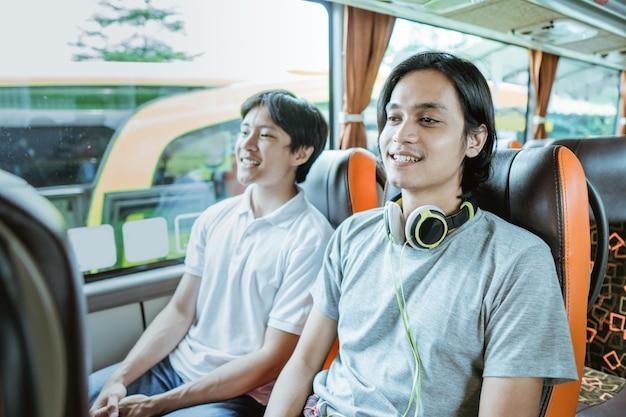 Un jeune garçon asiatique et un mec avec des écouteurs assis près de la fenêtre en profitant du trajet en bus