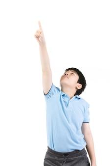 Jeune garçon asiatique pensant et pointant vers le haut en souriant.