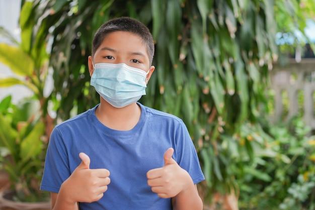 Jeune garçon asiatique porte un masque protecteur et montre les pouces vers le haut