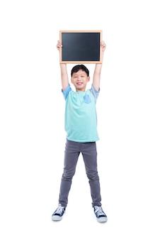 Jeune garçon asiatique tenant tableau et sourires sur fond blanc