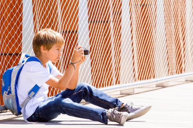 Jeune garçon assis avec un appareil photo numérique et prendre des photos dans la rue