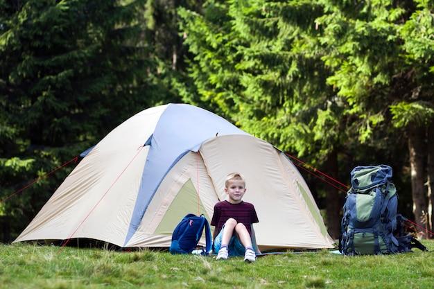 Jeune garçon assis devant une tente près de sacs à dos en prenant du repos