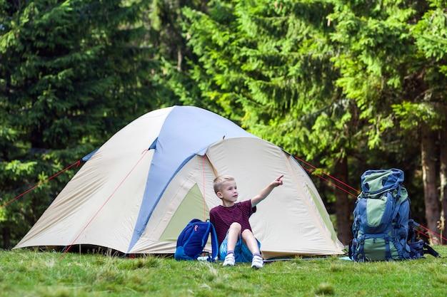 Jeune garçon assis devant une tente près de sacs à dos se reposer après une randonnée
