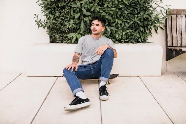 Jeune garçon assis sur une planche à roulettes