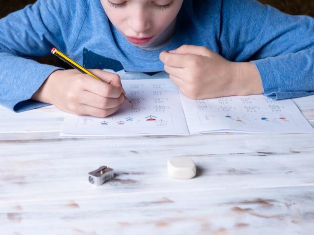 Jeune garçon assis à une table à la maison, étudiant et faisant ses devoirs