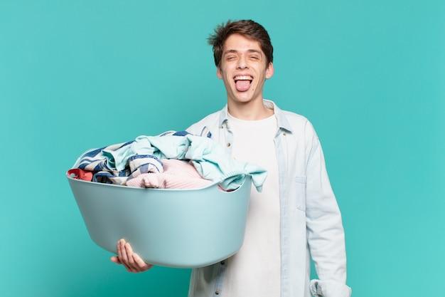 Jeune garçon avec une attitude joyeuse, insouciante, rebelle, plaisantant et tirant la langue, s'amusant à laver le concept de vêtements