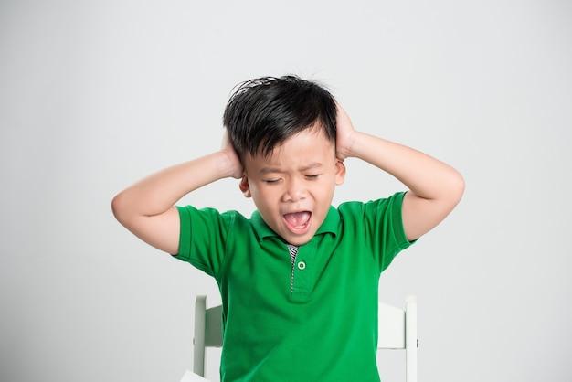 Jeune garçon aux yeux fermés couvrant les oreilles avec les mains