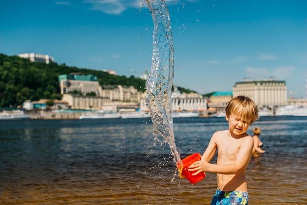 Jeune garçon aux yeux fermés renverse de l'eau sur la plage de la mer