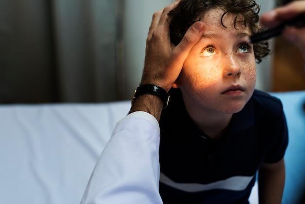 Jeune garçon ayant ses yeux vérifiés