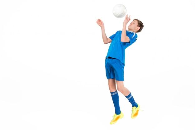 Jeune garçon avec ballon de foot faisant coup de pied volant